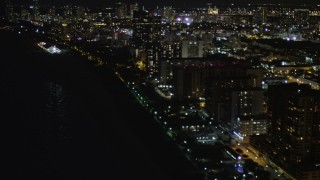 AX0023_105 - 5K stock footage aerial video of beachfront condos and hotels at night in Miami Beach, Florida