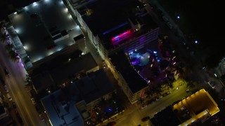 AX0023_116 - 5K stock footage aerial video bird's eye view of a South Beach hotel with bright lights at nighttime, Florida