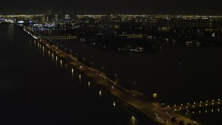 AX0023_127 - 5K stock footage aerial video of approaching the MacArthur Causeway with light traffic at night in Miami, Florida