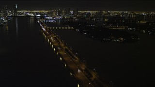 AX0023_128 - 5K stock footage aerial video fly over cars traveling on the MacArthur Causeway at night in Miami, Florida