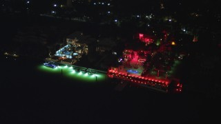 AX0023_132 - 5K stock footage aerial video flyby a waterfront hotel on Star Island with bright red lights at night in Florida