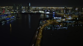 AX0023_135 - 5K stock footage aerial video tilt from the MacArthur Causeway to reveal skyscrapers in Downtown Miami at night in Florida