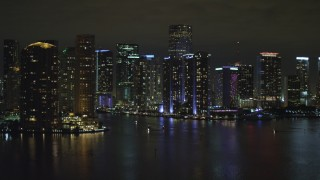 AX0023_153 - Aerial stock footage of 5K aerial \video tilt from the bay to reveal waterfront towers of the Downtown Miami at night, Florida