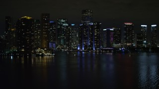 AX0023_153E - Aerial stock footage of 5K aerial \video tilt from the bay to reveal waterfront towers of the Downtown Miami at night, Florida