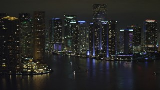 AX0023_154 - 5K stock footage aerial video approach tall high-rises by the Miami River at nighttime in Downtown Miami, Florida