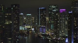 AX0023_155 - 5K stock footage aerial video fly over Miami River past skyscrapers at night in Downtown Miami, Florida