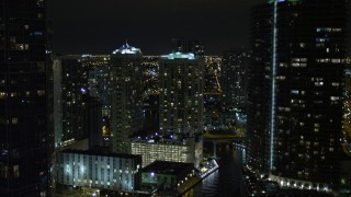 AX0023_155E - 5K stock footage aerial video fly over Miami River past skyscrapers at night in Downtown Miami, Florida