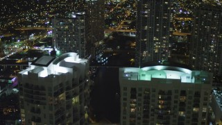 AX0023_157 - 5K stock footage aerial video fly over Brickell on the River rooftops and tilt to Miami River at night in Downtown Miami, Florida