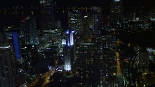 AX0023_158E - 5K stock footage aerial video tilt from elevated rail and office building to reveal skyscrapers at night in Downtown Miami, Florida