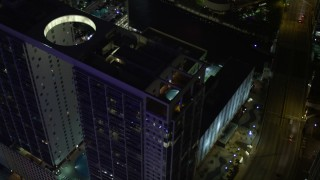 AX0023_168 - 5K stock footage aerial video approach 500 Brickell and tilt to rooftop pool at night in Downtown Miami, Florida