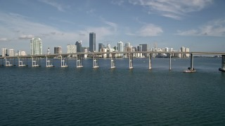 AX0024_052E - 5K stock footage aerial video tilt from Biscayne Bay to reveal Rickenbacker Causeway, Downtown Miami, Florida