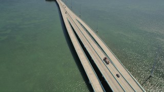 AX0025_054 - 5K stock footage aerial video follow Overseas Highway bridge over Lake Surprise, reveal Key Largo, Florida