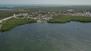 AX0025_055 - 5K stock footage aerial video of flying over Lake Surprise toward neighborhood, Key Largo, Florida