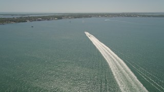 AX0025_059 - 5K stock footage aerial video of following two boats racing to shore across Blackwater Sound, Key Largo, Florida