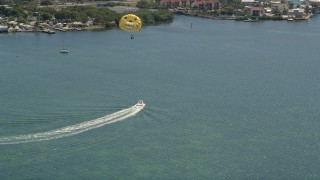 AX0025_061 - 5K stock footage aerial video of speedboat pulling parasailers on Blackwater Sound, Key Largo, Florida