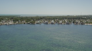 AX0025_064 - 5K stock footage aerial video of flying by homes on the shore of Blackwater Sound, Key Largo, Florida