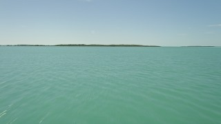 AX0025_075 - 5K stock footage aerial video of flying low over water, approaching mangroves on shore, Key Largo, Florida
