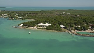AX0025_085 - 5K stock footage aerial video of flying by a home on the shore, Tavernier, Florida