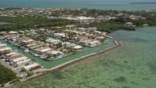 AX0025_087 - 5K stock footage aerial video of flying by waterfront homes on the shore, Tavernier, Florida