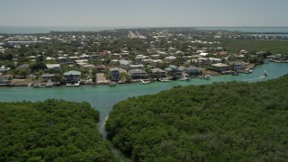 AX0025_090 - 5K stock footage aerial video of flying low over mangroves toward Tavernier Creek homes, Tavernier, Florida