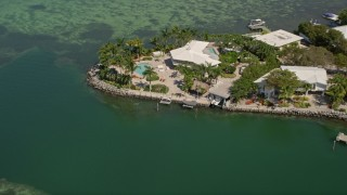 AX0025_093 - Aerial stock footage of 5K aerial  video of flying away from upscale home on the shore, Tavernier, Florida
