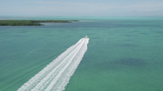 AX0025_095 - 5K stock footage aerial video of following a fishing boat speeding past mangroves, Tavernier, Florida
