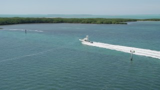 AX0025_097 - 5K stock footage aerial video of tracking a fishing boat speeding between mangroves, Tavernier, Florida