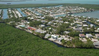 AX0025_104 - 5K stock footage aerial video of approaching homes on canals along shore, Islamorada, Florida