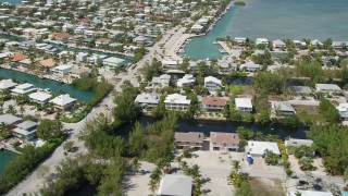 AX0025_105 - 5K stock footage aerial video of flying by homes on canals along shore, Islamorada, Florida