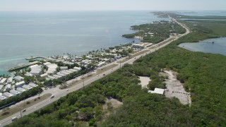 AX0025_106 - 5K stock footage aerial video of following Overseas Highway, passing resorts and marinas, Islamorada, Florida