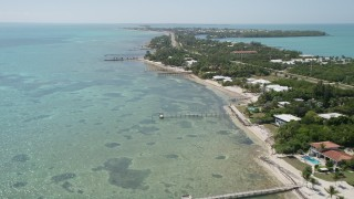 AX0025_126 - 5K stock footage aerial video of flying by homes on the coast, Islamorada, Florida