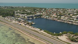 AX0025_129 - 5K stock footage aerial video fly by Overseas Highway, neighborhoods, buildings on canals, Islamorada, Florida