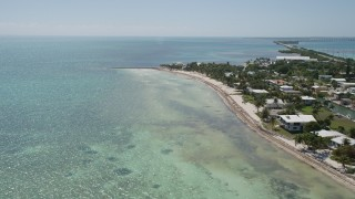 AX0025_130 - 5K stock footage aerial video of flying by coastal homes, approaching end of beach, Islamorada, Florida