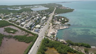AX0025_140 - 5K stock footage aerial video of following Overseas Highway past neighborhoods on the coast, Layton, Florida