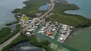 AX0025_152 - 5K stock footage aerial video of approaching Grassy Key and tilt down to neighborhood, Marathon, Florida