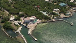 AX0025_156 - 5K stock footage aerial video of flying by a large home on shore of Grassy Key, Marathon, Florida