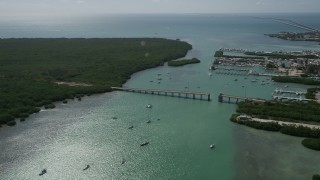 AX0026_011 - 5K stock footage aerial video fly over sailboats and fishing boats, reveal incomplete bridge, Boot Key, Marathon, Florida