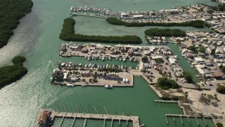 AX0026_012 - 5K stock footage aerial video of boats docked at a coastal marina, Marathon, Florida