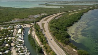 AX0026_045E - 5K stock footage aerial video of following Overseas Highway past Big Pine Key Fishing Lodge, Big Pine Key, Florida