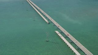 AX0026_055 - 5K stock footage aerial video of flying by Overseas Highway bridge, tilt up to the shore, Summerland Key, Florida