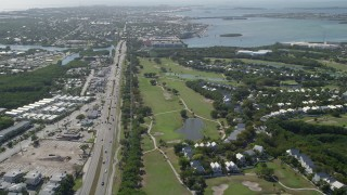 AX0026_058 - 5K stock footage aerial video follow Overseas Highway to Stock Island and Key West Golf Club, Key West, Florida