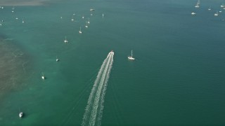 AX0026_083 - 5K stock footage aerial video of following a speedboat racing past moored sailboats, Key West, Florida