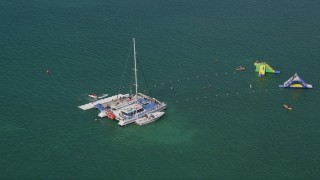 AX0026_087 - 5K stock footage aerial video of flying by swimmers on floats near catamaran in Key West, Florida