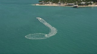 AX0026_091 - 5K aerial stock footage video of a jet skier near the shore of Key West, Florida