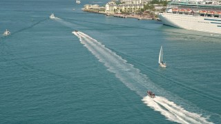 AX0026_099 - 5K stock footage aerial video of a speedboat racing across water and tilt to more boats in Key West, Florida