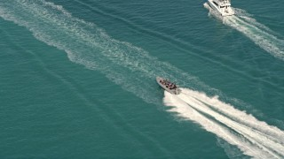AX0026_101 - 5K stock footage aerial video of tracking speedboat racing across water by Key West, Florida