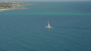 AX0026_107 - 5K stock footage aerial video of flying by a catamaran near the shore of Key West, Florida