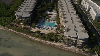 AX0027_006 - 5K stock footage aerial video of following the coast, revealing 1800 Atlantic Vacation Rentals, Key West, Florida