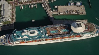 AX0027_018 - 5K stock footage aerial video of approaching Royal Caribbean Cruise Ship docked, tilt down, Key West, Florida