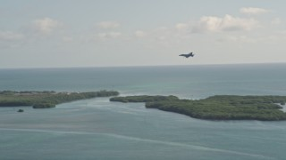 AX0027_036 - 5K stock footage aerial video of tracking an F-18 landing at Naval Air Station Key West, Key West, Florida